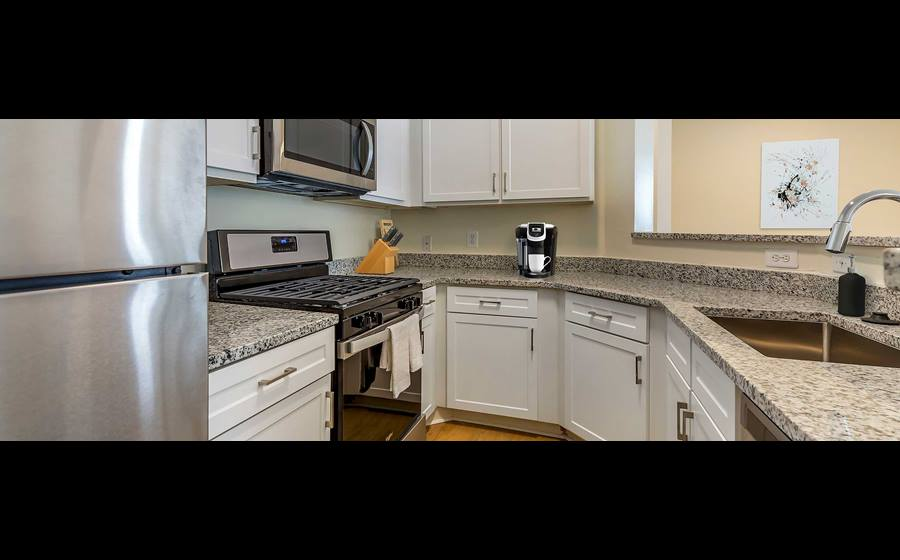 Newly renovated Finish Package II kitchen with white cabinetry, stainless steel appliances and granite countertops