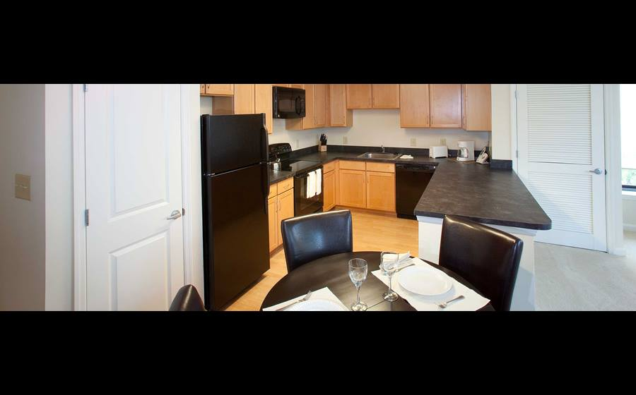 Dining rea and kitchen with black appliances, black countertops and hard surface flooring