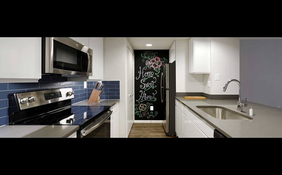 Newly Renovated Finish Package V kitchen with grey quartz countertops, blue tile backsplash, white cabinetry, stainless steel appliances, and hard surface plank flooring