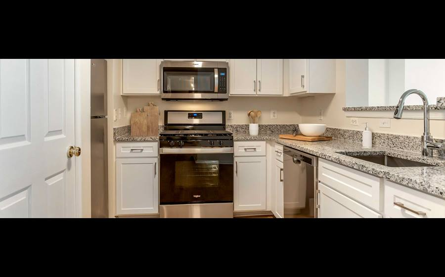 Finish Package II kitchen with white cabinetry, granite countertops, stainless steel appliances and hard surface flooring