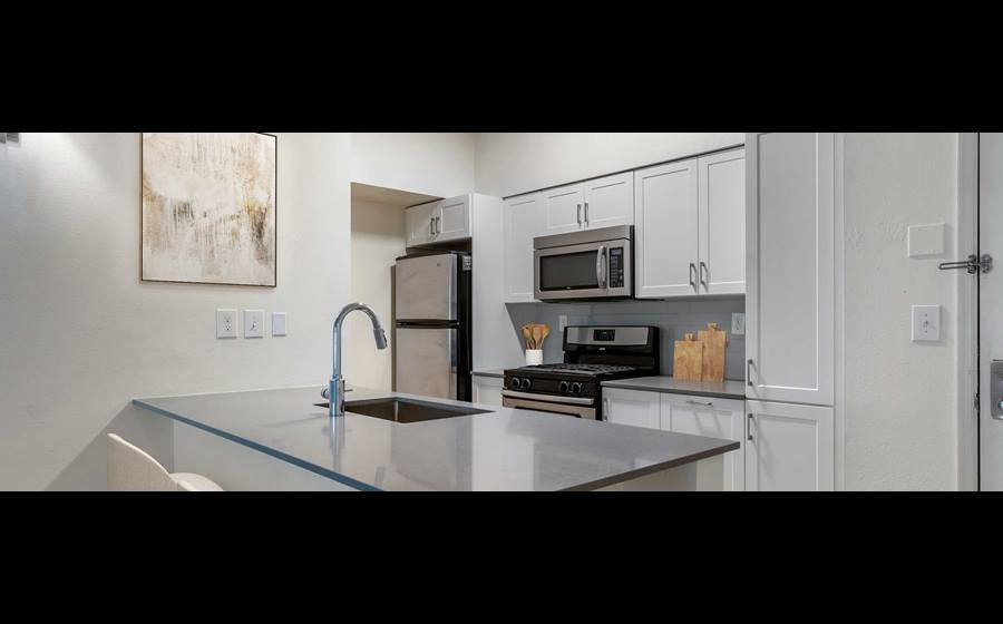 Newly renovated Finish Package IV kitchen with grey quartz countertops, white cabinetry, stainless steel appliances, tile backsplash, and hard surface flooring
